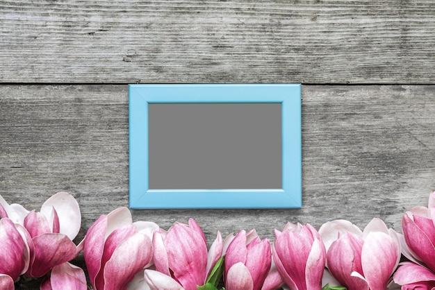 素朴な木製のテーブルにピンクのマグノリアの花を持つ空白のフォトフレーム。平干し。上面図。モックアップ。春のコンセプト