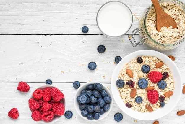 健康的な朝食の食材。ラズベリーとブルーベリー、牛乳、白い木製のテーブル上のナッツと自家製のオート麦