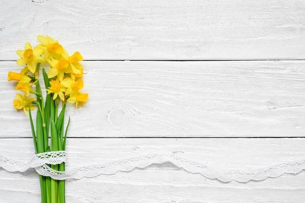 白い木製のテーブルの上の黄色い水仙の花の春の花の花束