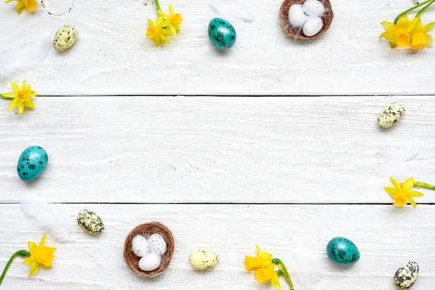 卵と白い木製のテーブルの春の花で作られたイースターフレーム。イースター組成