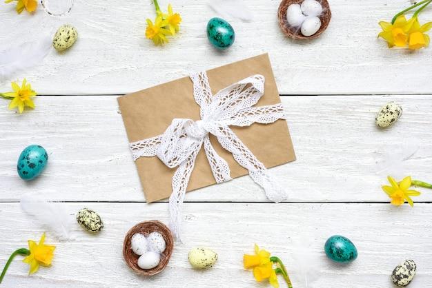 ウズラの卵、春の花、羽で作られたフレーム内の封筒とイースターのグリーティングカード