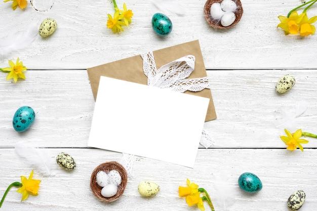 イースターエッグ、春の花、白い木製のテーブル上の羽で作られたフレームのイースターのグリーティングカード。イースター組成。コピースペースを持つトップビュー