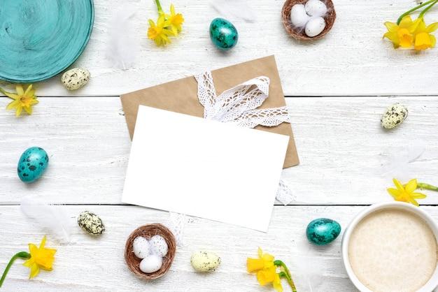 ウズラの卵、カプチーノのカップ、白い木製のテーブルの春の花で作られたフレームでイースターのグリーティングカード