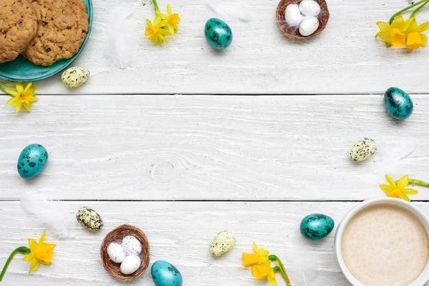 イースターエッグ、カップのカプチーノ、春の花、白い木製のテーブルのビスケットで作られたフレーム。イースター組成