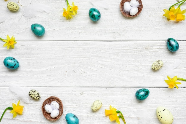 イースターエッグと白い木製のテーブルの春の花で作られたフレーム。イースター組成