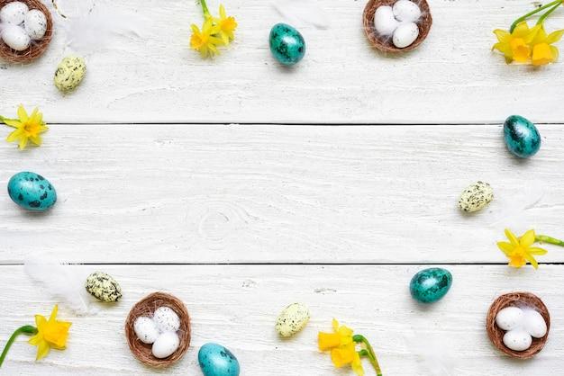 イースターエッグ、春の花、白い木製のテーブル上の羽で作られたフレーム。イースター組成