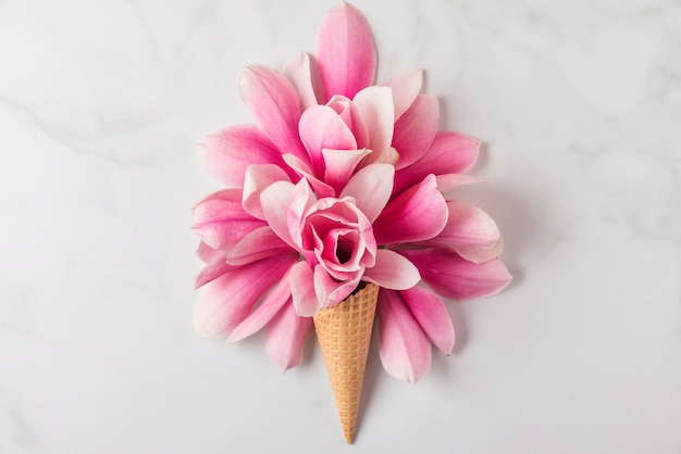 春のピンクのマグノリアの花の組成を持つアイスクリームコーン。最小限の春のコンセプト。平置き