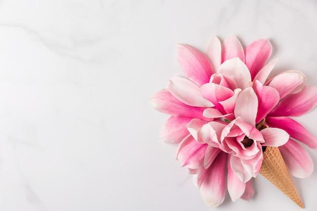 アイスクリームコーンのピンクのマグノリアの花で作られた創造的なレイアウト。平干し。上面図