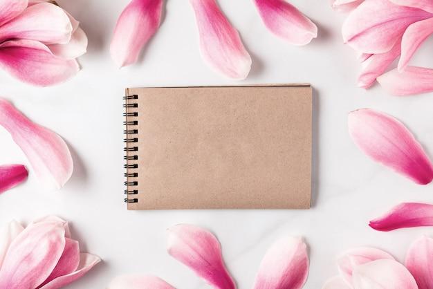 ピンクのマグノリアの花で作られたフレームで空白のグリーティングカード。平干し。春のコンセプト