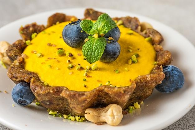 Веганский сырой манго чизкейк со свежей черникой, мятой и фисташками. концепция здорового вегетарианского глютена