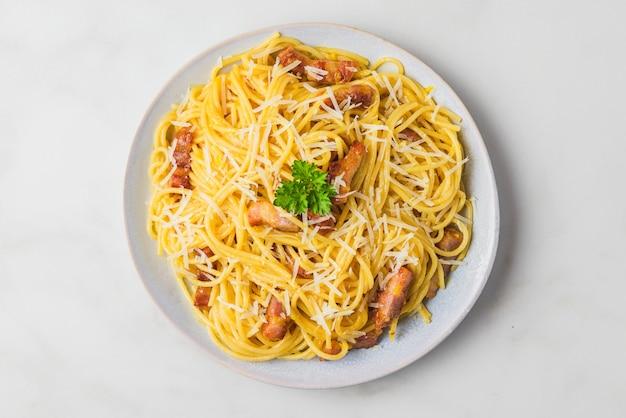 Паста карбонара, спагетти с гуансиалом, яйцом, твердым сыром пармезан и петрушкой. традиционная итальянская кухня