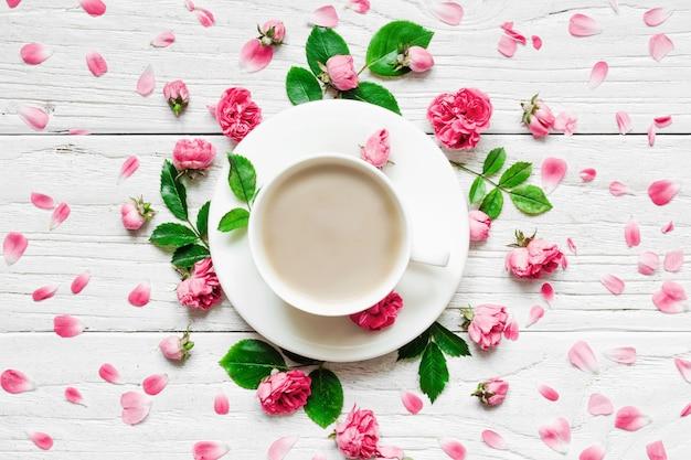Композиция цветов. рамка сделанная из свежих роз цветет с чашкой капучино на белой деревянной предпосылке. плоская планировка