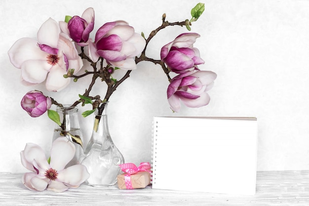 ピンクのマグノリアの花、空のカード、白い木製の背景にギフトボックスで作られた創造的なレイアウト
