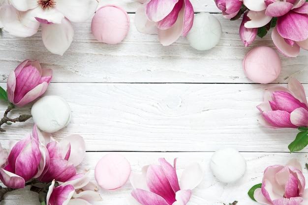白い木製のテーブルの上のマカロンとピンクのマグノリアの花で作られたフレーム。モックアップ。フラット横たわっていた。上面図