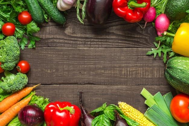 テーブルの上の新鮮な収穫野菜の品揃えで作られたフレーム。上面図