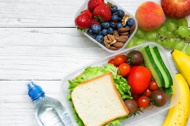 Школьные ланч-боксы с бутербродом, фруктами, овощами и бутылкой воды и копией пространства