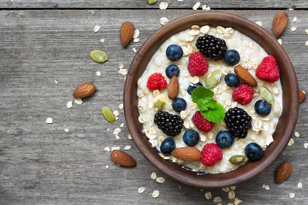 果実とナッツの素朴な木製の背景に健康的な朝食のボウルにオートミールのお粥