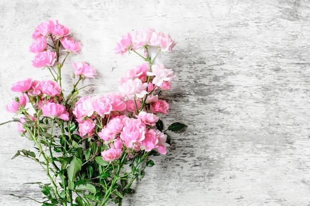 白い素朴な木製の背景にピンクのバラの花の花束