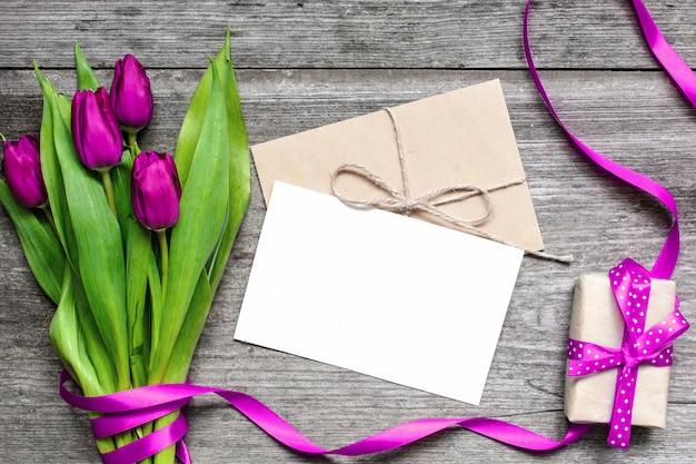 Пустая белая открытка и конверт с фиолетовыми тюльпанами и подарочной коробкой