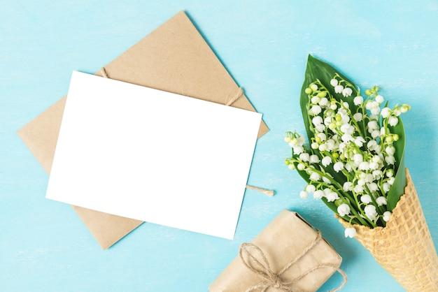 青の背景にギフトボックスとワッフルコーンの春のスズランの花と空白のグリーティングカード。モックアップ。平置き