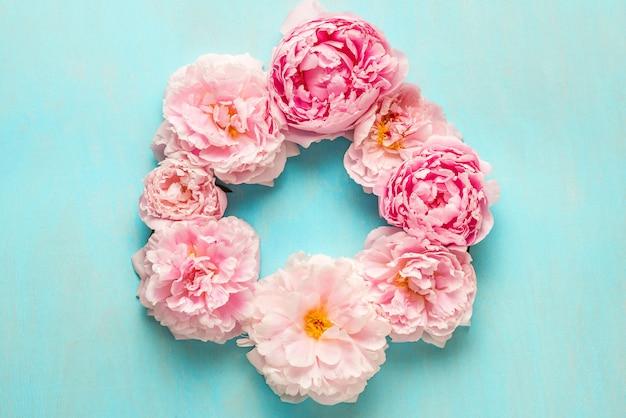 花の組成物。コピースペースを持つ青い木製の背景にピンクの牡丹の花で作られたフレーム。フラットレイ