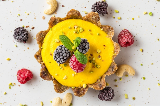 Веганская еда десерт. сырой веганский желтый кешью манго пирог с замороженными ягодами, фисташками и мятой. закрыть