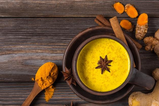 伝統的なインドの飲み物ターメリックラテまたはゴールデンミルク、シナモン、ジンジャー、アニス、コショウ、ターメリック。上面図