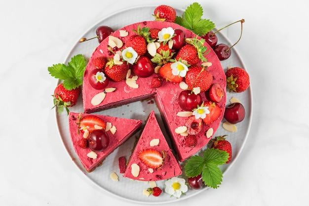 新鮮なイチゴ、チェリー、花が白のプレートでスライスされたベリーのチーズケーキ。上面図