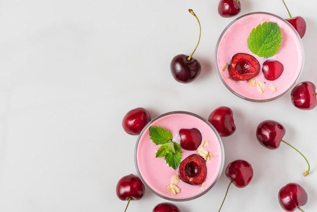 Свежий летний вишневый йогурт с ягодами, овсом и мятой в очках на белом мраморе. вид сверху