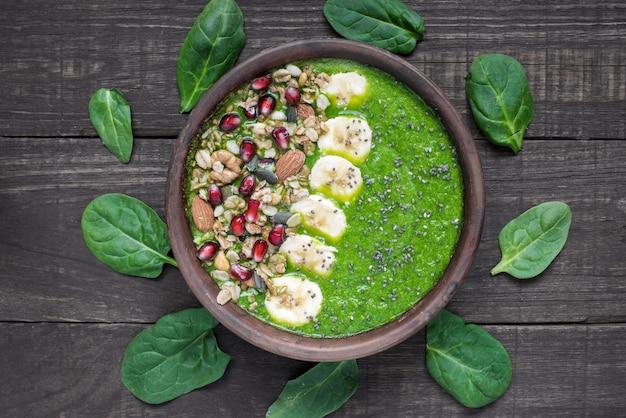 Зеленый детокс завтрак смузи чаша с гранола, банан, гранат, тыква и семена чиа
