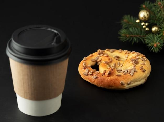 Бумажный стаканчик с горячим напитком, кофе или чаем. рядом свежий крендель и елка. крупный план.
