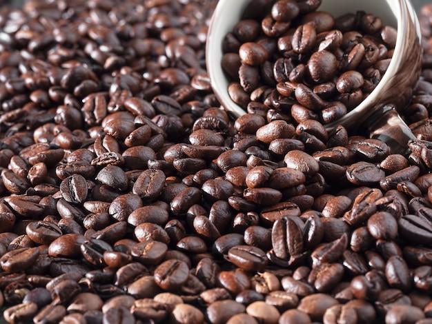 Жареные кофейные зерна. свежие ароматные темные кофейные зерна и чашка эспрессо.