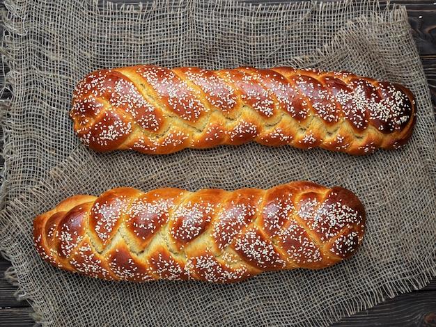 Свежеиспеченный сладкий плетеный хлеб на ткани