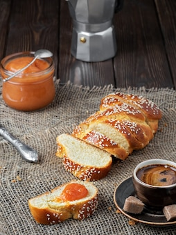 Свежеиспеченный сладкий плетеный хлеб, кофе и джем