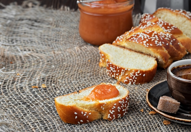 Нарезанный сладкий плетеный хлеб, кофе и джем