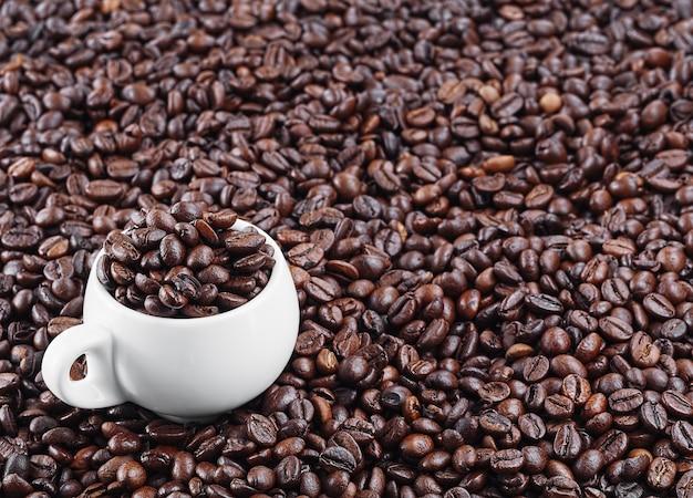 Жареные кофейные зерна. свежий ароматный темный кофе. белая чашка для эспрессо стоит в кофейных зернах.