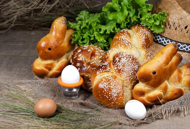 新鮮なイースターのペストリー、うさぎ型のパン、卵、ロールパンは黄麻布の上にあります