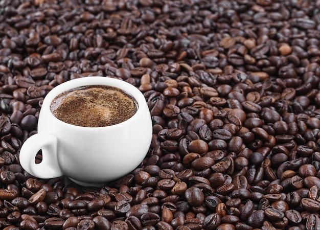 В кофейных зернах стоит белая чашка с ароматным эспрессо. жареные кофейные зерна. свежий ароматный темный кофе. крупный план.