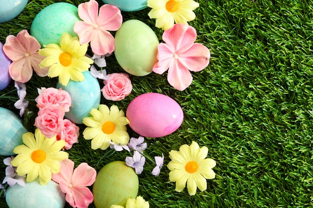 Красочные пасхальные яйца на траве с цветами фона