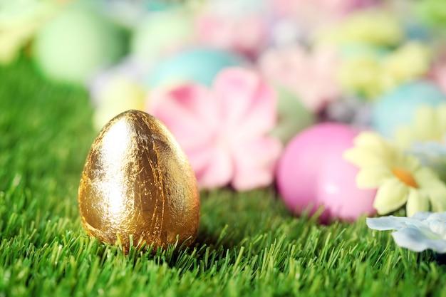 Красочные пасхальные яйца на траве с золотым яйцом