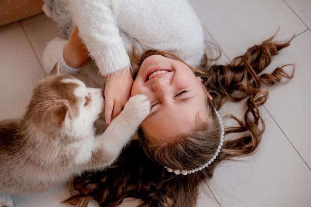 ハスキーの子犬と遊ぶ少女