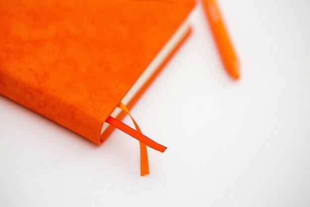 オレンジ色のメモ帳とボールペン、白い表面、テキスト用のスペース