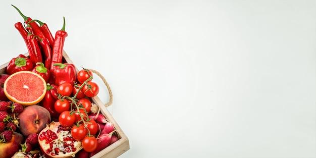 白い背景の上の新鮮な赤い野菜と果物の木製トレイ。健康的な食事のベジタリアンコンセプト。