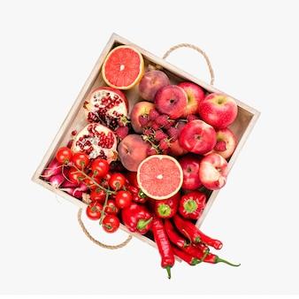 女の子は、白い背景の上に新鮮な赤い野菜や果物の木製トレイを保持しています。健康的な食事のベジタリアンコンセプト。
