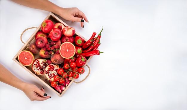 女の子は、灰色の背景に新鮮な赤い野菜や果物の木製トレイを保持しています。健康的な食事のベジタリアンコンセプト。