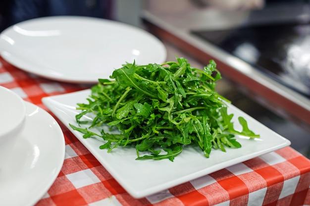 白い正方形板に新鮮なルッコラのサラダ