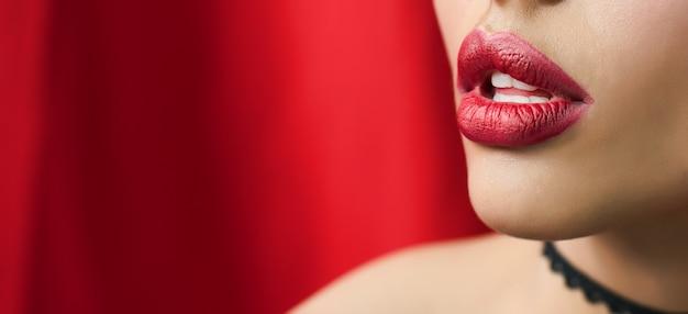 美しい赤い唇のクローズアップショットを持つ女性