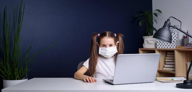 Дистанционное обучение онлайн-образование. школьница в медицинской маске учиться на дому, работать на ноутбуке ноутбука и делать домашнее задание в школе. карантин коронавируса.