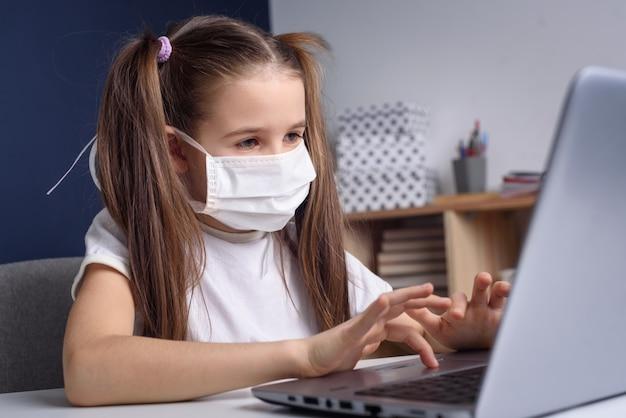オンライン教育の遠隔学習。自宅で勉強して、ラップトップのノートブックで働いて、学校の宿題をしている医療マスクの女子高生。コビッド検疫の概念