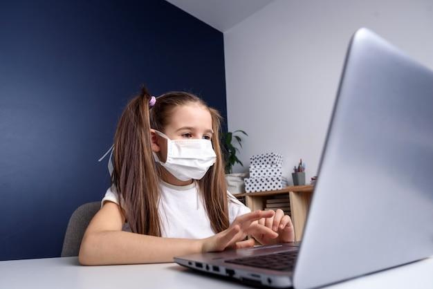 Дистанционное обучение онлайн-образование. школьница в медицинской маске учиться на дому, работать на ноутбуке ноутбука и делать домашнее задание в школе. концепция коварного карантина